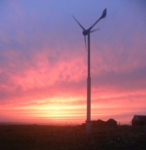 Domestic-scale wind turbine at sunset